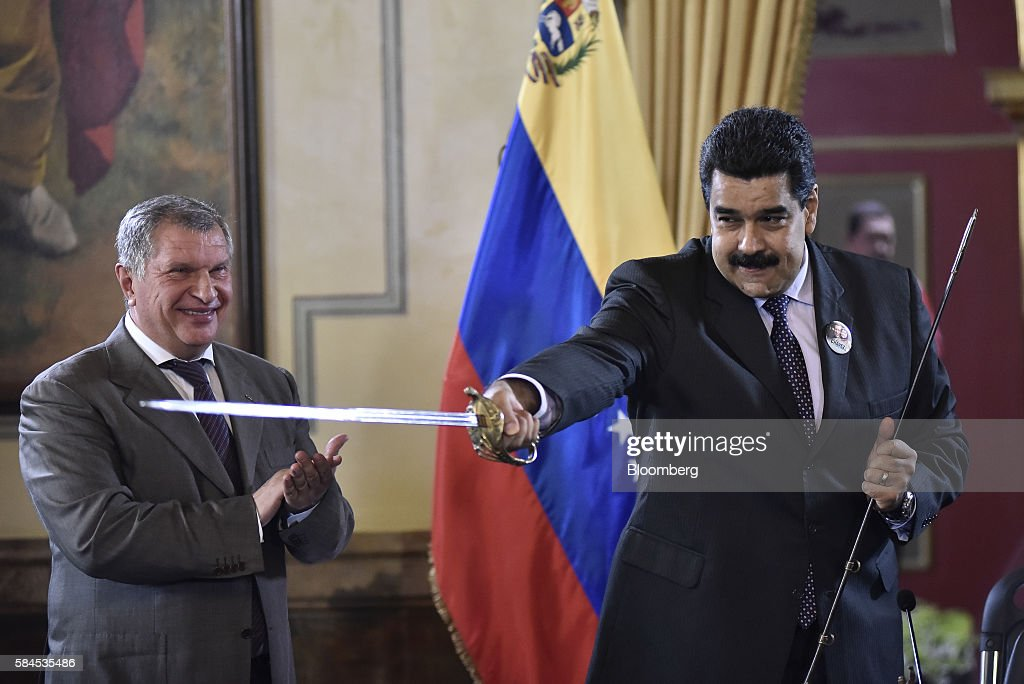 Nicolas Maduro, president of Venezuela, right, brandishes a sword given to him as a gift by Igor Sechin, chief executive officer of Rosneft PJSC, after Eulogio del Pino, president of Petroleos de Venezuela SA (PDVSA), not pictured, and Sechin signed natural gas deals in Caracas, Venezuela, on Thursday, July 28, 2016. The agreements included a deal for Rosneft to participate in the Mariscal Sucre natural gas project. Photographer: Carlos Becerra/Bloomberg via Getty Images
