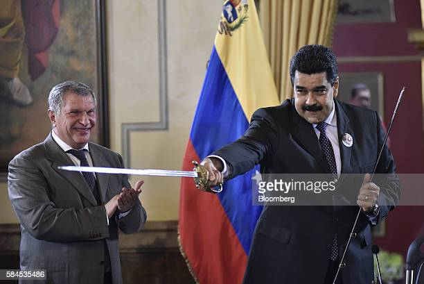 Nicolas Maduro president of Venezuela right brandishes a sword given to him as a gift by Igor Sechin chief executive officer of Rosneft PJSC after...