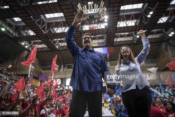 Nicolas Maduro Venezuela's president and Cilia Flores Venezuela's first lady wave to attendees during a rally in Caracas Venezuela on Wednesday Feb 7...