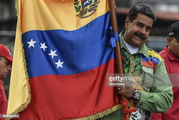 Nicolas Maduro Venezuela's president holds a flag during a campaign rally in Caracas Venezuela on Thursday May 17 2018 Maduro said the May 20...