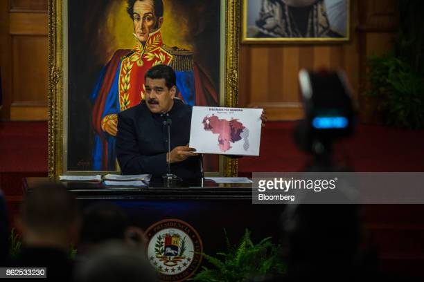 Nicolas Maduro Venezuela's president holds a map to show the numbers of states won by the United Socialist Party of Venezuela during a press...