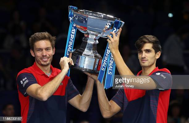 Nicolas Mahut and PierreHugues Herbert of France lift the trophy after their doubles final match victory against Raven Klaasen of South Africa and...