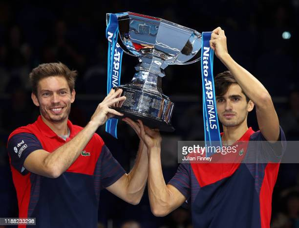 Nicolas Mahut and Pierre-Hugues Herbert of France lift the trophy after their doubles final match victory against Raven Klaasen of South Africa and...