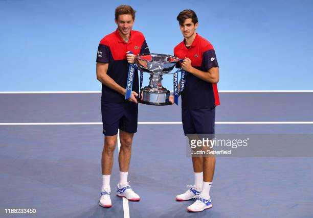 Nicolas Mahut and Pierre-Hugues Herbert of France pose with the trophy after their doubles final match victory against Raven Klaasen of South Africa...