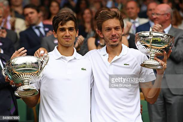 Nicolas Mahut of France and PierreHugues Herbert of France hold their trophies following victory in the Men's Doubles Final against Julien Benneteau...