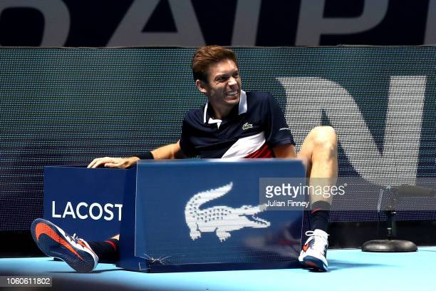 Nicolas Mahut of France partner of Pierre-Hugues Herbert collides with the advertising boards during their doubles round robin match against Oliver...