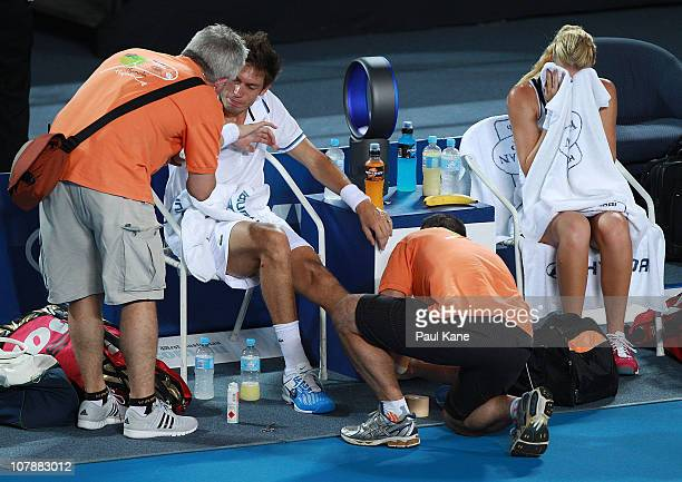 Nicolas Mahut of France receives medical attention on the court injuring his ankle during his mixed doubles match partnered with Kristina Mladenovic,...