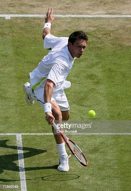 Nicolas Mahut of France returns a backhand to Roger Federer of Switzerland during day five of the Wimbledon Lawn Tennis Championships at the All...