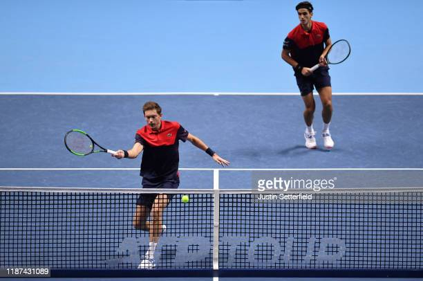 Nicolas Mahut, playing partner of Pierre-Hugues Herbert of France plays a forehand in their doubles match against Kevin Krawietz of Germany and...