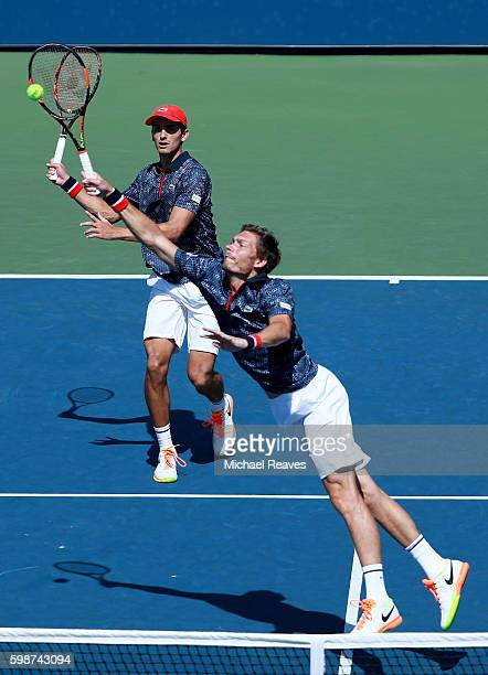 Nicolas Mahut reaches for a shot with partner PierreHugues Herbert against Robin Haase of Netherlands and Artem Sitak of New Zealand on Day Five of...