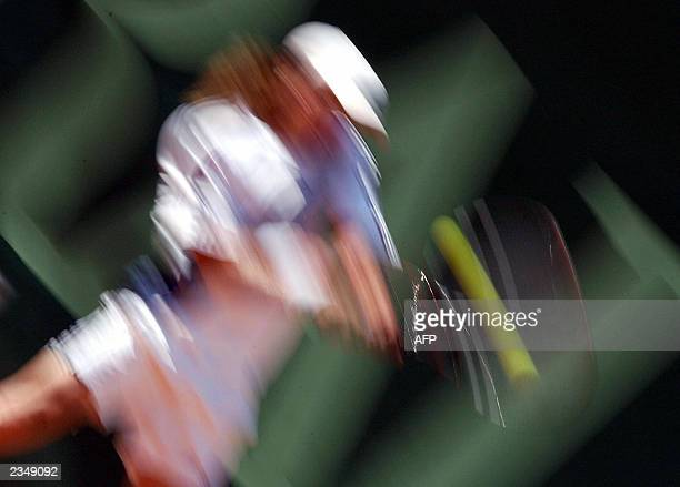 Nicolas Massu of Chile blured by slow camera shutter returns the ball to Mariano Zabaleta of Argentina during the semifinal match of the Generaliopen...