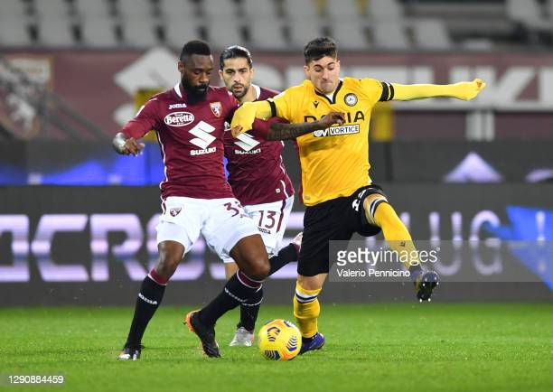 Nicolas Nkoulou of Torino F.C. And Ignacio Pussetto of Udinese Calcio battle for the ball during the Serie A match between Torino FC and Udinese...