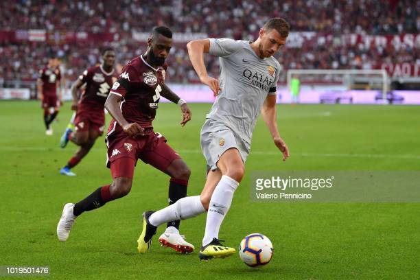 Nicolas Nkoulou of Torino FC competes for the ball with Edin Dzeko of AS Roma during the Serie A match between Torino FC and AS Roma at Stadio...