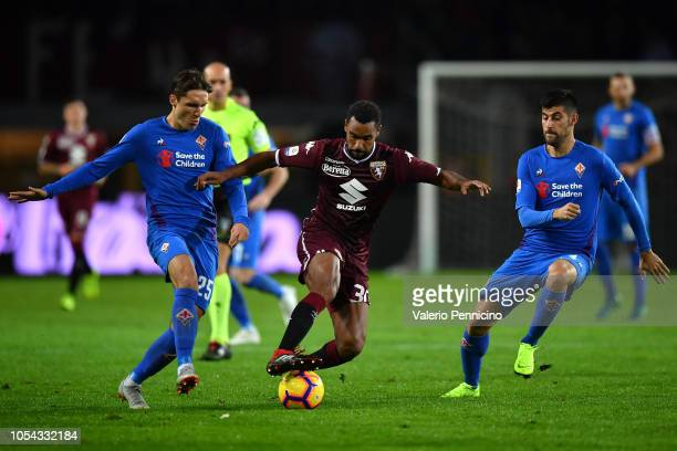 Nicolas Nkoulou of Torino FC is challenged by Marco Benassi and Federico Chiesa of ACF Fiorentina during the Serie A match between Torino FC and ACF...