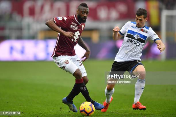 Nicolas Nkoulou of Torino FC is challenged by Remo Freuler of Atalanta BC during the Serie A match between Torino FC and Atalanta BC at Stadio...