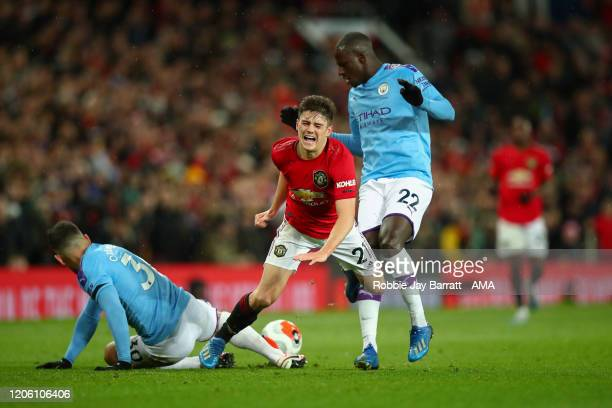 Nicolas Otamendi and Benjamin Mendy of Manchester City crackle Daniel James of Manchester United during the Premier League match between Manchester...
