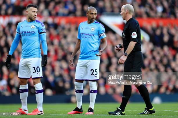 Nicolas Otamendi and Fernandinho of Manchester City complain to referee Mike Dean during the Premier League match between Manchester United and...