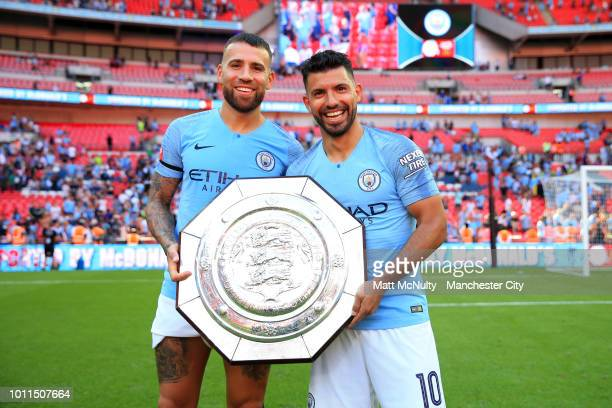 Nicolas Otamendi and Sergio Aguero of Manchester City celebrate with the FA Community Shield Trophy following their sides victory in the FA Community...