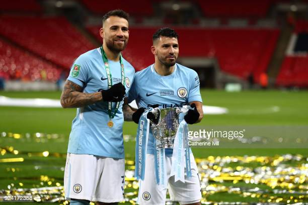 Nicolas Otamendi and Sergio Aguero of Manchester City celebrate with the trophy after the Carabao Cup Final between Arsenal and Manchester City at...