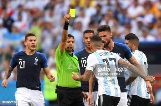 Nicolas Otamendi of Argentina is shown a yellow card by referee Alireza Faghani during the 2018 FIFA World Cup Russia Round of 16 match between...