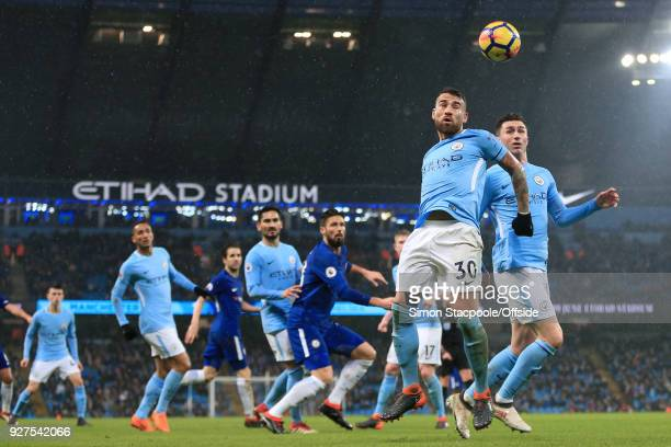 Nicolas Otamendi of Man City heads the ball alongside teammate Aymeric Laporte of Man City during the Premier League match between Manchester City...