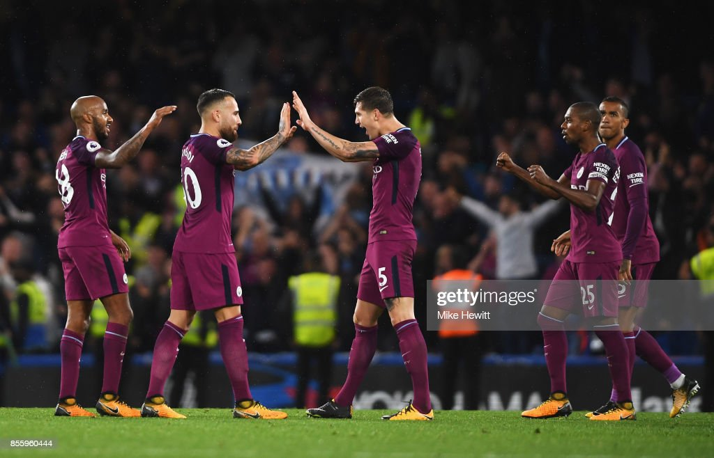 Nicolas Otamendi of Manchester City and John Stones of Manchester City celebrate victory after the Premier League match between Chelsea and Manchester City at Stamford Bridge on September 30, 2017 in London, England.