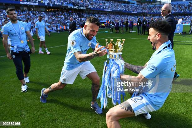 Nicolas Otamendi of Manchester City and Kyle Walker of Manchester City celebrate with The Premier League Trophy after the Premier League match...