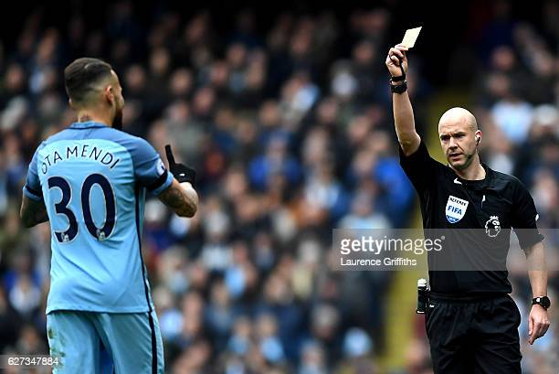 Nicolas Otamendi of Manchester City is shown a yellow card by referee Anthony Taylor during the Premier League match between Manchester City and...