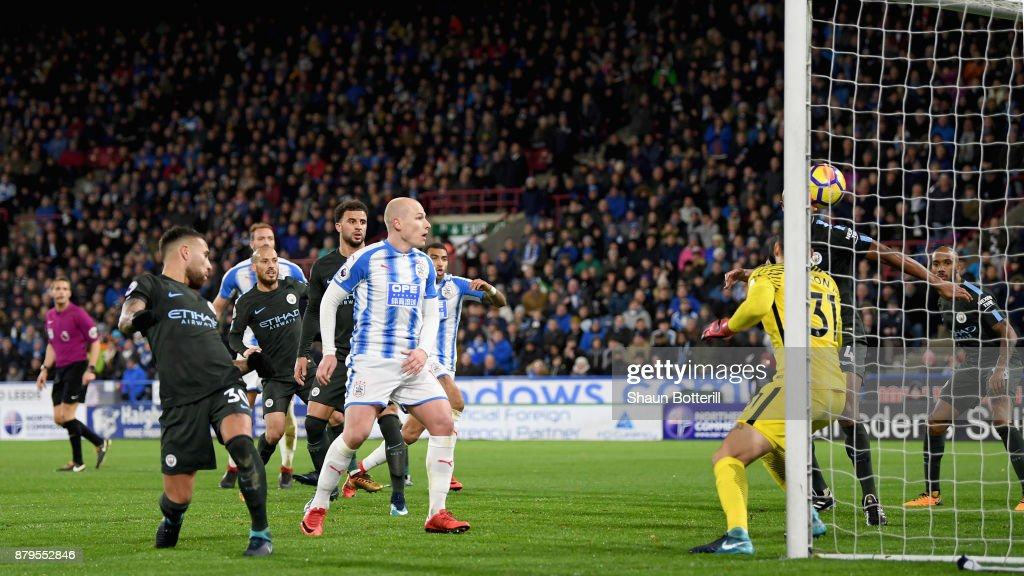 Nicolas Otamendi of Manchester City scores the first own goal as Aaron Mooy of Huddersfield Town look on during the Premier League match between Huddersfield Town and Manchester City at John Smith's Stadium on November 26, 2017 in Huddersfield, England.