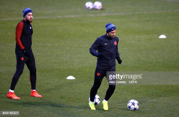 Nicolas Otamendi of Manchester City watches on as Sergio Aguero of Manchester City warms up during a Manchester City training session and press...