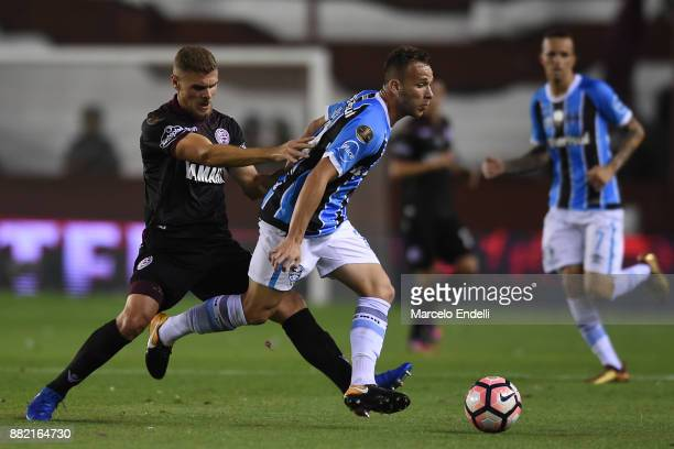 Nicolas Pasquini of Lanus fights for the ball with Arthur of Gremio during the second leg match between Lanus and Gremio as part of Copa Bridgestone...