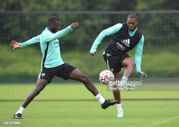 Nicolas Pepe and Nuno Tavares of Arsenal during a training session at London Colney on July 30, 2021 in St Albans, England.