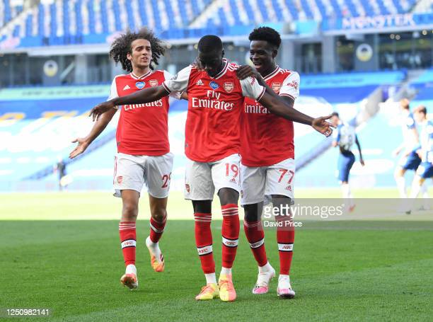 Nicolas Pepe celebrates scoring a goal for Arsenal with Matteo Guendouzi and Bukayo Saka during the Premier League match between Brighton Hove Albion...