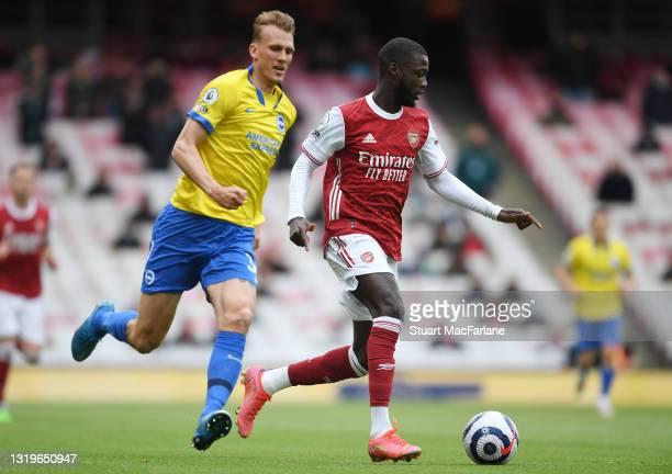 Nicolas Pepe of Arsenal breakas past Dan Burn of Brighton during the Premier League match between Arsenal and Brighton & Hove Albion at Emirates...