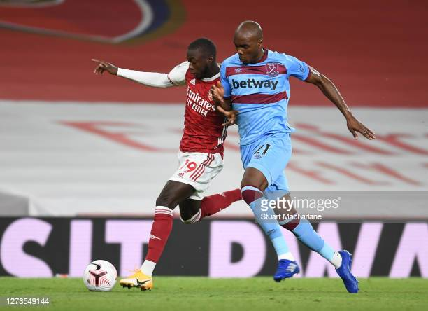 Nicolas Pepe of Arsenal breaks past Angelo Ogbonna of West Ham during the Premier League match between Arsenal and West Ham United at Emirates...