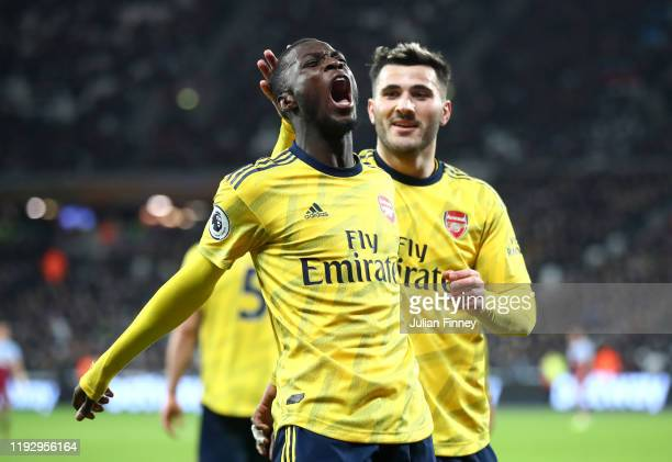 Nicolas Pepe of Arsenal celebrates after scoring his sides second goal with Saed Kolasinac during the Premier League match between West Ham United...
