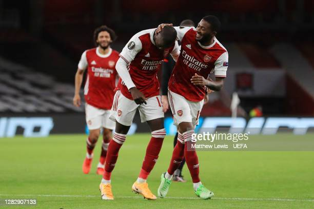 Nicolas Pepe of Arsenal celebrates with teammate Ainsley Maitland-Niles after scoring his team's third goal during the UEFA Europa League Group B...