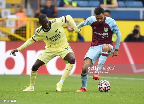 Nicolas Pepe of Arsenal challenged by Dwight McNeil of Burnley during the Premier League match between Burnley and Arsenal at Turf Moor on September...
