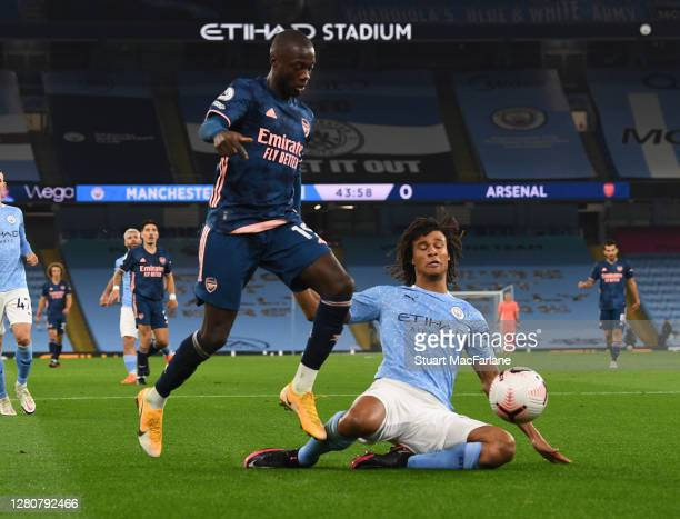 Nicolas Pepe of Arsenal challenged by Nathan Ake of Man City during the Premier League match between Manchester City and Arsenal at Etihad Stadium on...