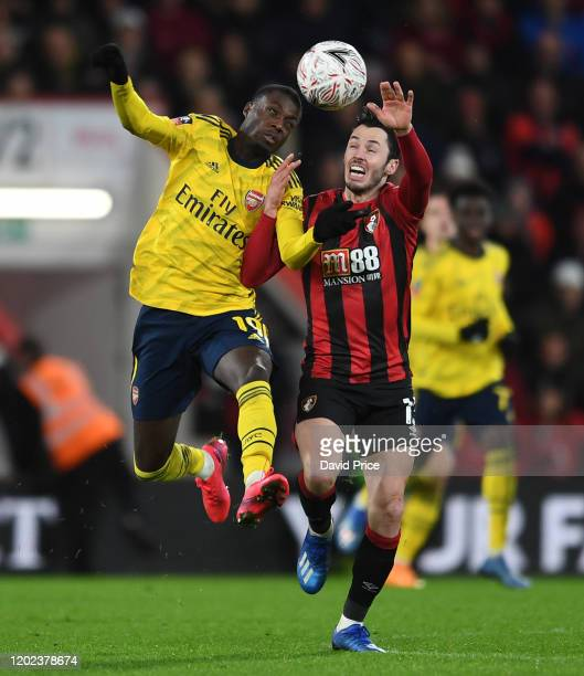 Nicolas Pepe of Arsenal challenges Adam Smith of Bournemouth during the FA Cup Fourth Round match between AFC Bournemouth and Arsenal at Vitality...
