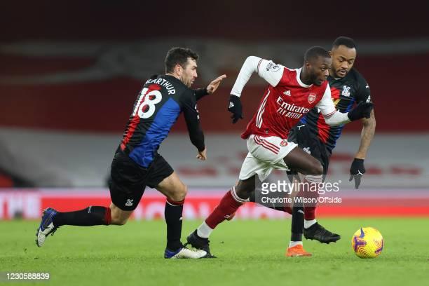 Nicolas Pepe of Arsenal gets between James McArthur of Crystal Palace and Jordan Ayew of Crystal Palace during the Premier League match between...