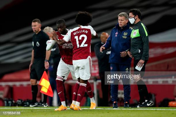 Nicolas Pepe of Arsenal greets Willian of Arsenal as he is substituted off and Nicolas Pepe is substituted on during the Premier League match between...