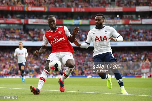 Nicolas Pepe of Arsenal is challenged by Danny Rose of Tottenham Hotspur during the Premier League match between Arsenal FC and Tottenham Hotspur at...