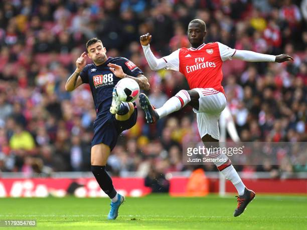Nicolas Pepe of Arsenal is challenged by Diego Rico of AFC Bournemouth during the Premier League match between Arsenal FC and AFC Bournemouth at...