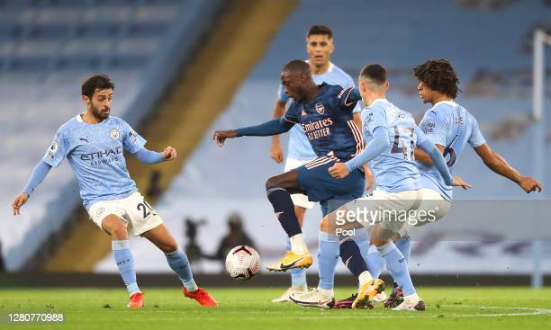 Nicolas Pepe of Arsenal is challenged by Phil Foden Nathan Ake and Bernardo Silva of Manchester City during the Premier League match between...