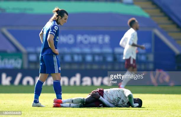Nicolas Pepe of Arsenal looks to be injured as Caglar Soyuncu of Leicester City looks on during the Premier League match between Leicester City and...