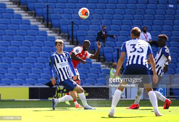 Nicolas Pepe of Arsenal scores his team's first goal past Matthew Ryan of Brighton and Hove Albion during the Premier League match between Brighton...