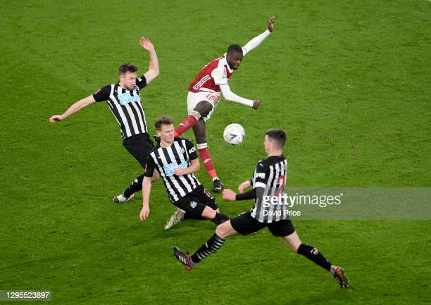 Nicolas Pepe of Arsenal shoots under pressure from Paul Dummett, Matt Ritchie and Ciaran Clark of Newcastle during the FA Cup Third Round match...