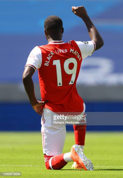 Nicolas Pepe of Arsenal takes a knee in support of the Black Lives Matter movement prior to the Premier League match between Brighton & Hove Albion...