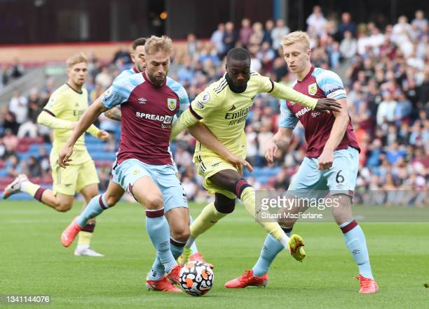 Nicolas Pepe of Arsenal takes on Charlie Taylor and Ben Mee of Burnley during the Premier League match between Burnley and Arsenal at Turf Moor on...